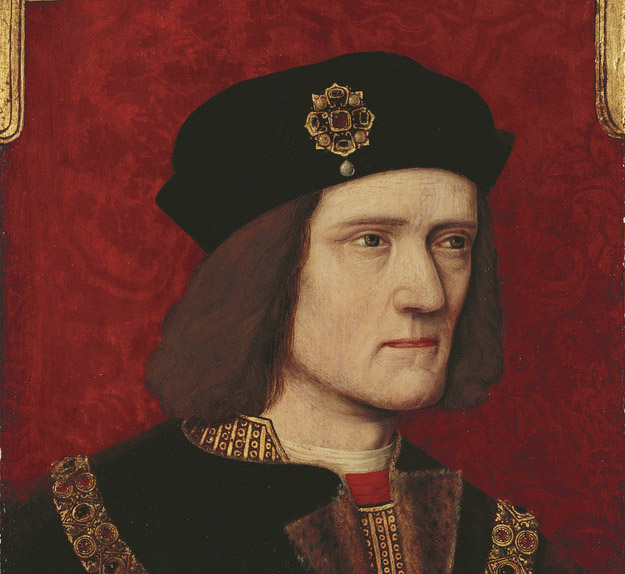 A head and shoulders portrait of Richard III, on a red background with gold embellishment in the upper corners. His face is turned slightly to the right, with a serious expression; at the bottom of the frame, his hands are shown in the middle of removing a ring from his right little finger. The heights of his shoulders are visibly uneven. He wears a black robe, possibly fur-lined, over a gold patterned doublet with a flash of red at the collar. A chain of office hangs across his chest. His black hat bears a gold, ruby, and pearl brooch in the shape of a stylised rose.